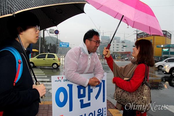 '김해을' 국회의원 선거에 나선 새누리당 이만기 후보가 18일 아침 비가 내리는 속에 김해 장유1동사무소 앞 거리에서 비옷을 입고 출근인사하면서 지나가는 시민들과 이야기를 나누고 있다.