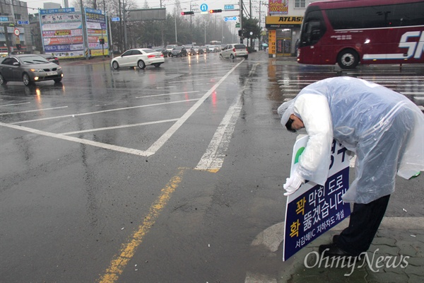 '김해을' 국회의원 선거에 나선 더불어민주당 김경수 후보가 18일 아침 비가 내리는 속에 김해 내외동사거리에서 비옷을 입고 출근인사하고 있다.