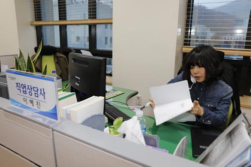 이혜진 씨가 구직자와 전화 상담을 하며 관련 서류를 뒤적이고 있다. 이 씨는 하루 평균 30∼40명과 상담을 한다.