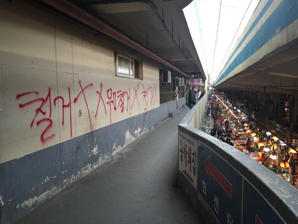 붉은 글씨로 가득한 수산시장 벽면.