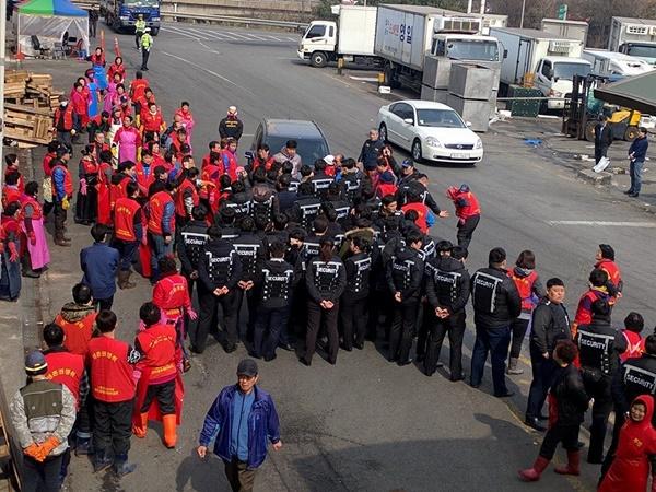 등 뒤에 'security'라고 적힌 옷을 입은 사람들이 수산시장으로 들어오는 차량을 막아서고 있다. (사진 : 노량진수산시장 현대화비상대책총연합회)