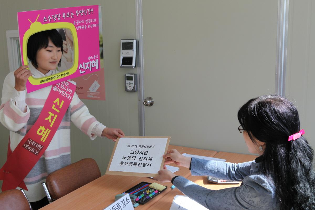 신지혜 노동당 고양시갑 국회의원 후보가 지난 24일 티브이 모양의 피켓을 쓰고 덕양구선거관리위원회에 후보등록을 하고 있다.