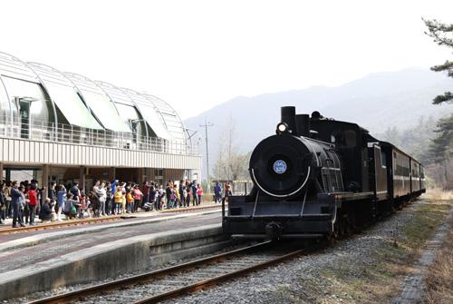침곡역에 잠시 멈춘 증기기관열차. 역에는 증기기관열차가 지난 길을 달리는 레일바이크를 타려는 여행객들이 줄을 지어 기다리고 있다.