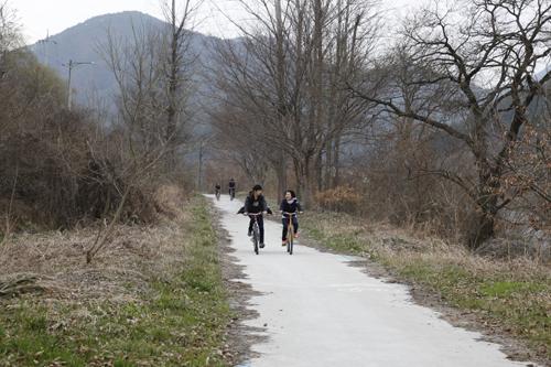 강바람을 가르며 달리는 자전거들. 섬진강변을 따라 이어진 자전거도로 풍경이다.