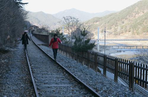 철길의 레일 위를 걷는 여행객들. 섬진강 둘레길에서는 섬진강변의 철길을 따라 걷는 색다른 재미까지 느낄 수 있다.