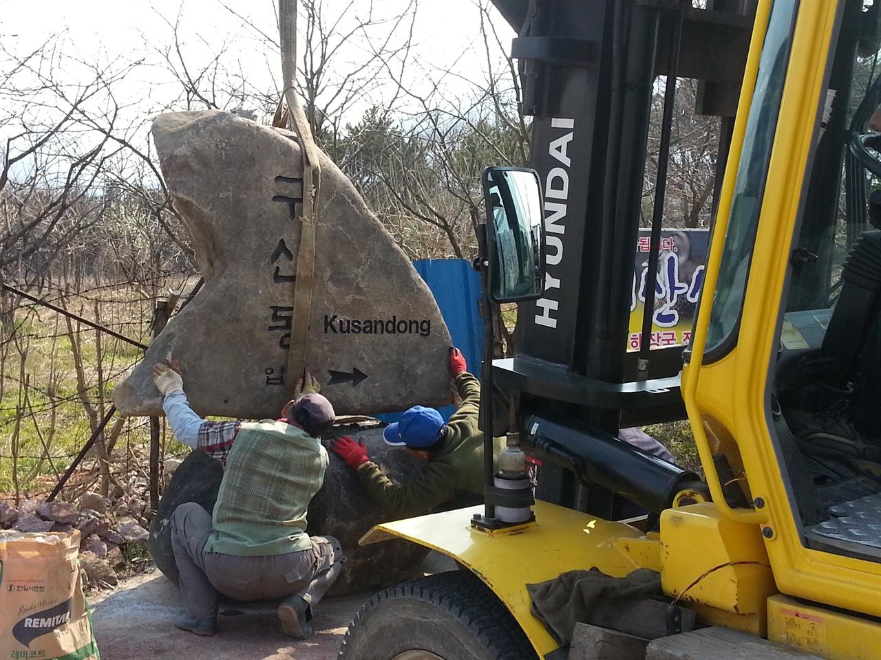 작업중 짐을 옮기는 중장비차가 안내 돌을 들어서 밑돌에 올리고 있다.