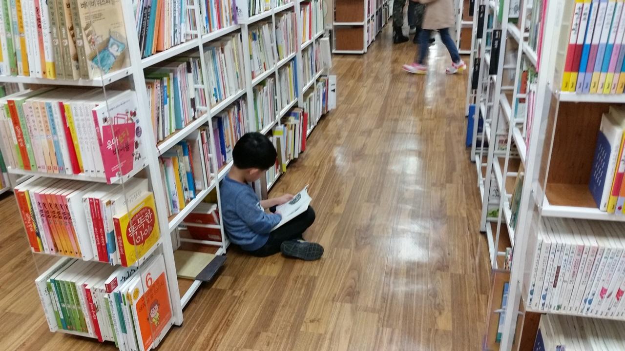 아빠를 닮은 아이 서점 통로 바닥에 앉아 책을 읽고 있는 둘째 아들.