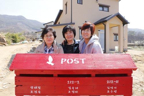 우체통 앞에 선 세 자매. 집앞에 세 집의 우체통을 한꺼번에 만들어 놓았다.