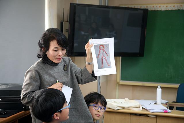 여수부영초등학교 5학년 3반 교실에서 감성수업을 한 조선미 수석교사가 학생이 그린 그림 내용에 대한 발표를 듣고 있다
