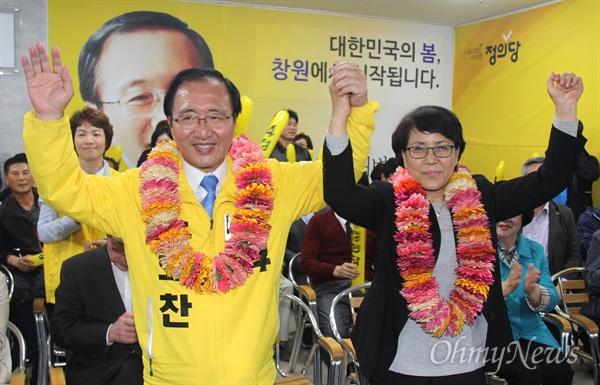 '창원성산' 국회의원선거에서 당선한 정의당 노회찬 후보가 13일 저녁 선거사무소에서 부인 김지선씨와 꽃다발을 받은 뒤 손을 들어 보이고 있다.