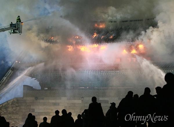 10일 밤 서울 숭례문에서 화재가 발생해 시민들이 무너져 내리는 숭례문을 바라보며 안타까워 하고 있다.
