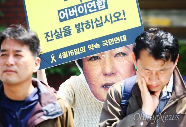 """""""어버이연합 진실을 밝히십시오"""" 한국진보연대 회원들이 29일 오전 서울 종로구 청운효자 주민센터 앞에서 기자회견을 열고 청와대-국정원-전경련-어버이연합 게이트 진상규명을 촉구하던 중 피켓 뒤로 박근혜 대통령 대형가면이 보이고 있다."""