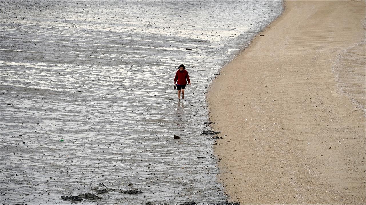 펜션 옆에 쌓인 모래톱을 걷는 사람.