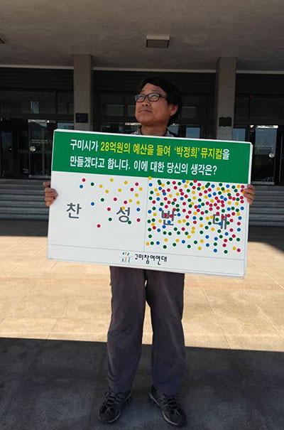 구미참여연대 회원이 구미시청 본관 앞에서 1인시위를 하고 있다. '박정희 뮤지컬' 찬반은 시민들에게서 받은 것이다.
