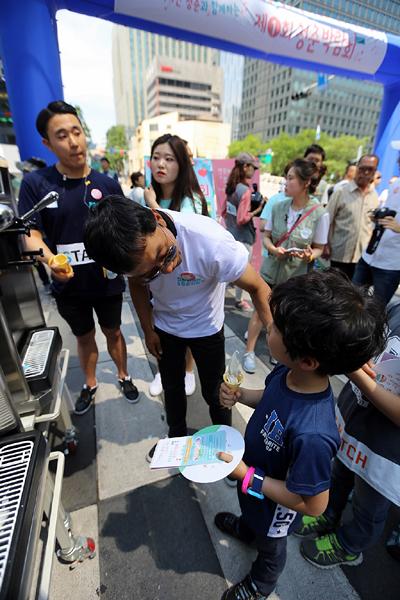 김제동씨가 한 아이에게 소프트콘을 건네고 있다.