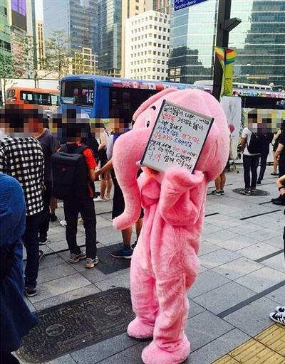 """지난 21일, 강남역 10번 출구 추모 현장에 나타난 분홍코끼리. 그가 나타나기 전날 일베(일간베스트 저장소)에 """"코끼리 인형탈 입고 강남역 가서 피켓들 예정이다""""라는 글이 쓰인 것으로 미루어 분홍코끼리 탈을 쓴 사람이 일베 회원이라는 추측도 나왔다."""