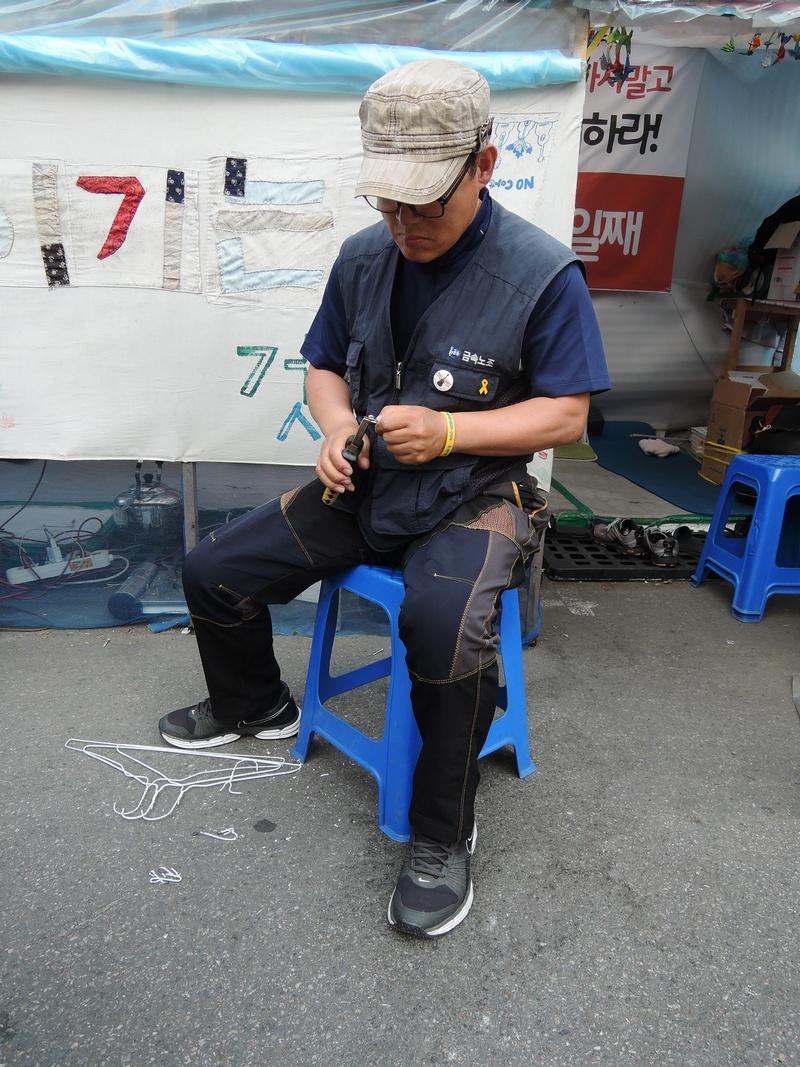봉가이버라는 별명을 가진 김경봉. 옷걸이를 잘라 모기장 고리를 만들고 있다.