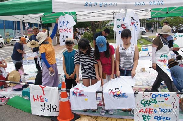 일요일인 17일 오전부터 성주군청 앞마당에서 아이들과 엄마들이 함께 '사드 반대' 티셔츠 글씨와 그림을 그리고 있다.