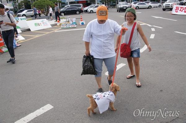 17일 오후 성주군청 앞에서 촛불집회에서 사용할 피켓 등을 만든 한 주민이 딸과 함께 강아지에게 '사드 철회'라고 쓴 옷을 입혔다.