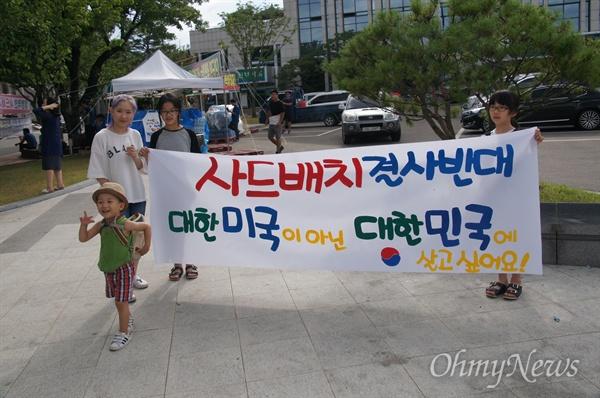 15일 오후 성주군청 앞에서 한 가족이 '대한미국이 아닌 대한민국에 살고 싶습니다'라고 쓴 현수막을 붙들고 있다.