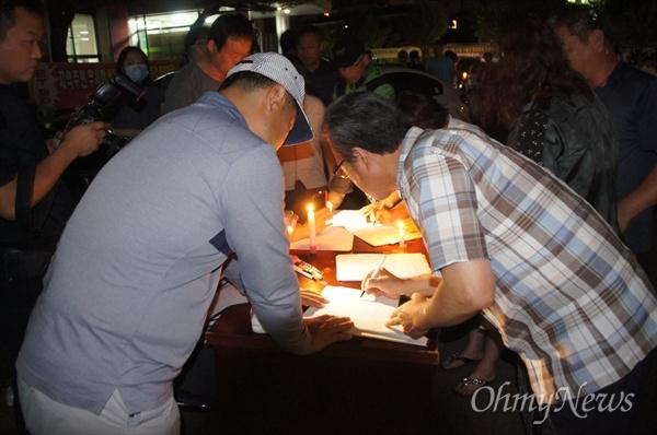사드 배치에 반대하는 성주군 새누리당 당원들이 17일 오후 8시부터 열린 촛불집회에서 탈당계를 작성하고 있다.