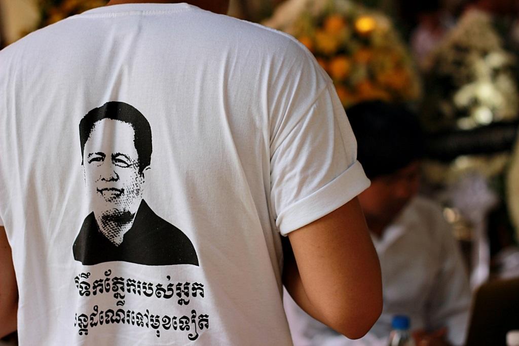 껨 레이의 얼굴이 그려진 티셔츠를 입은 시민. 여야를 가리지 않는 날카로운 비판과 정치평론으로 캄보디아 국민들의 사랑을 받았던 그에 대한 국민들의 추모열기를 보여준다.