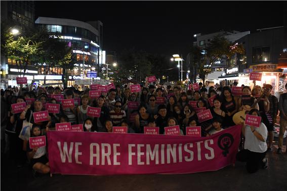 """집회 참석자들이 """"we are feminists""""라는 현수막과 손피켓을 들고 있다"""