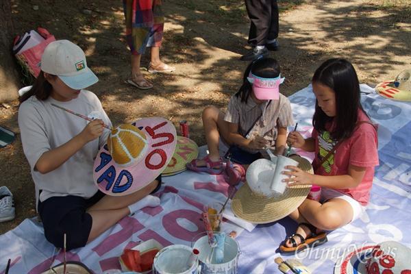 사드 철회를 요구하는 성주군민들이 소통하고 있는 SNS '1318+'가 제안해 7일 오후 성밖숲으로 소풍을 간 주민들과 아이들이 밀짚모자에 '사드 아웃'을 그리고 있다.
