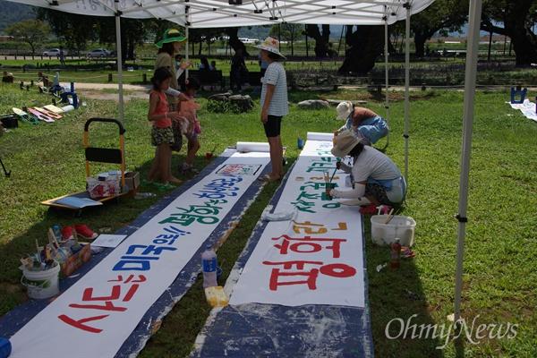 사드 철회를 요구하는 성주군민들의 SNS모임 '1318+'가 성밖숲으로 소풍을 나와 오프라인 모임을 가진 가운데 일부 주민들이 현수막천에 사드반대 글씨를 붓으로 쓰고 있다.