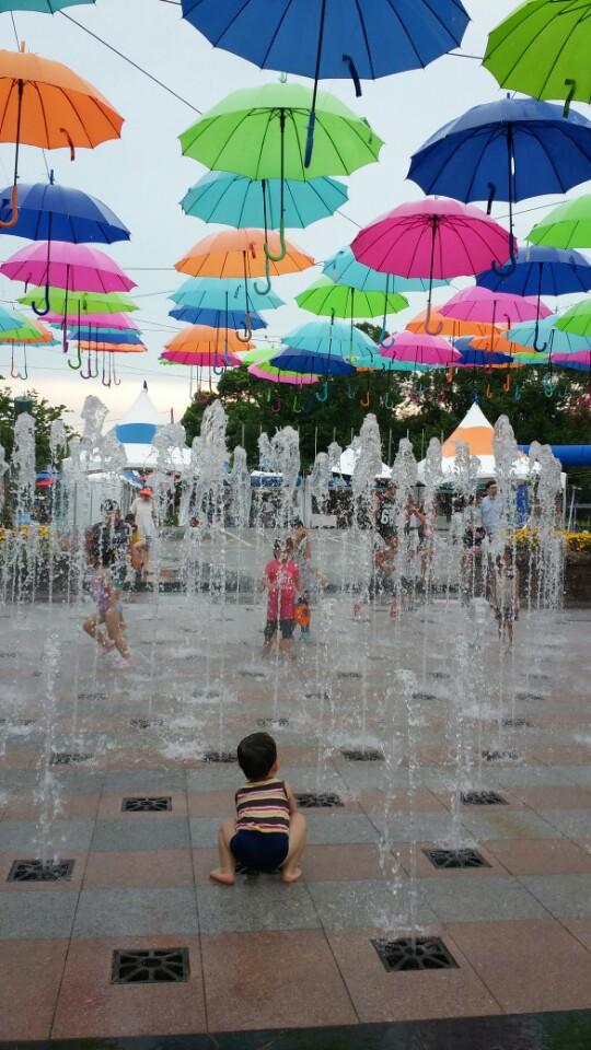 나도 끼워 줘요 축제 현장에 마련된 물놀이 현장에서 어린 아이가 치솟는 분수에 그 속으로 뛰어들기를 주저하는 모습