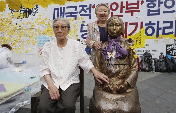14일 오후 서울 종로구 중학동 주한 일본대사관 앞에서 '세계 일본군 위안부 기림일'을 맞아 열린 '나비 문화제'에 참석한 김복동 할머니가 소녀상 옆 빈 의자에 앉아있다. 오른쪽은 길원옥 할머니.