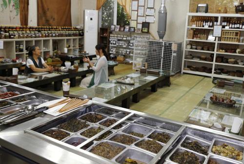 슬로시티 약초밥상의 내부 모습. 36가지 약초반찬이 진열된 식단 너머로 식탁이 줄지어 놓여 있다.