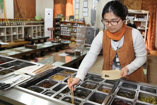 슬로시티 약초밥상을 운영하고 있는 장정인 씨가 약초 반찬을 그릇에 덜고 있다. 장 씨는 최금옥 씨의 며느리다.