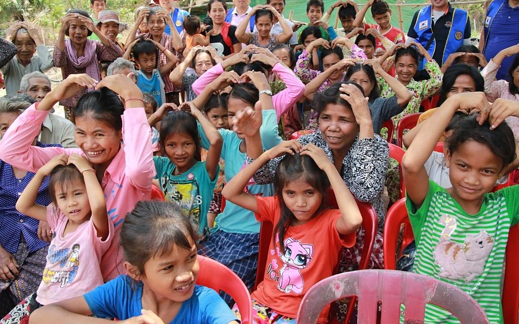 캄보디아 현지를  방문한 한국 봉사단체가 제공하는 생핌품과 간식을 받기 위해  마을 앞 공터에 모여 든 시골마을 주민들.