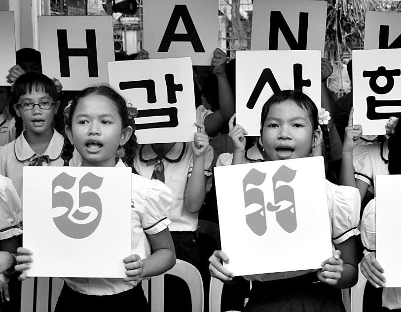 후원물품을 기증한 한국의 독지가의 방문을 앞두고, 감사하다는 한국어와 크메르어 팻말을 들어보이고 있는 캄보디아 초등학생들.