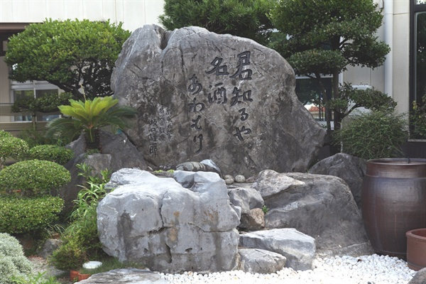 """마사히로 주조장의 입구에 새겨진, """"그대는 아는가 아와모리 명주를""""이라는 사카구치의 말."""
