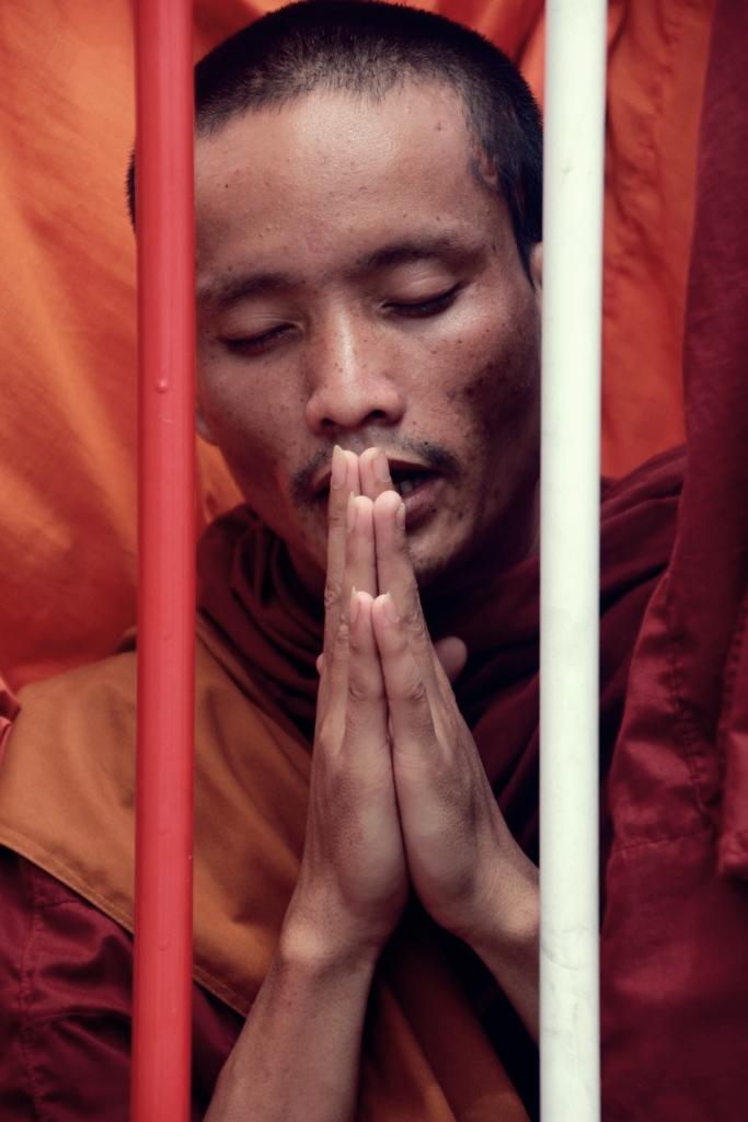시위진압을 위해 경찰이 쳐놓은 바리케이트를 사이에 두고 한 승려가 최근 구속된 사회운동가들의 석방을 바라며 간절한 기도를 올리고 있다.