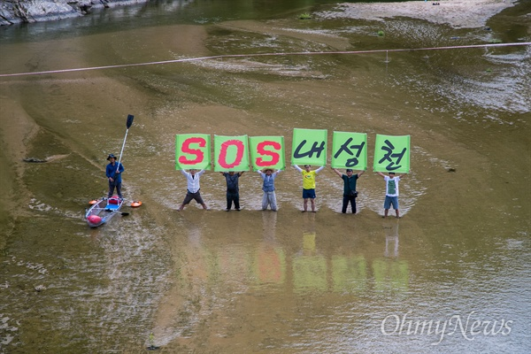 <오마이뉴스> 10만인클럽, 불교환경연대, 환경운동연합, 대한하천학회 회원들이 27일 오후 경북 예천 내성천 일대에서 강 보존을 위해 'SOS내성천'이 적힌 피켓을 들고 강 위에 서 있다.