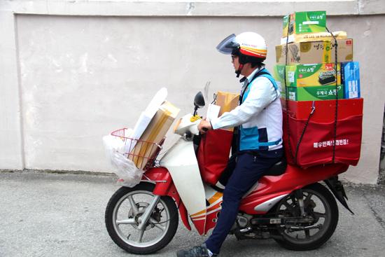 7일 아침, 오토바이 한가득 선물을 싣은 집배원이 시동을 걸고 있다.