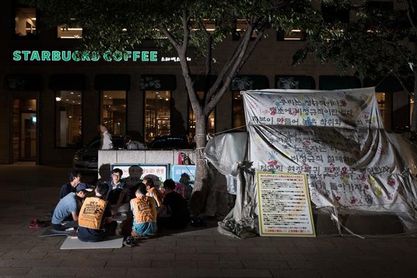 해고 노동자들의 천막 농성장 한 발짝 너머 스타벅스 커피숍은 냉기로 가득 차 있는데, 비닐천막 안은 후끈하기만 하다.
