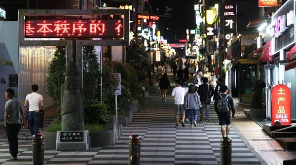 지난 20일 밤 중국인들로 붐비는 바오젠거리 모습. 입구에는 중국인 관광객을 환영한다면서도 '무단횡단, 쓰레기 투척 등 기본질서를 지키지 않는 행위에 대해서는 처벌하겠다'고 경고하는 중국어로 된 제주지방경찰청의 메시지가 보인다.