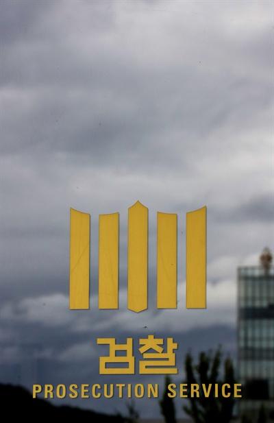 먹구름과 검찰 로고 지난 2016년 8월 28일 오후 서울 서초구 서울중앙지검 유리창에 새겨진 검찰 로고가 먹구름에 둘러싸여 있다.