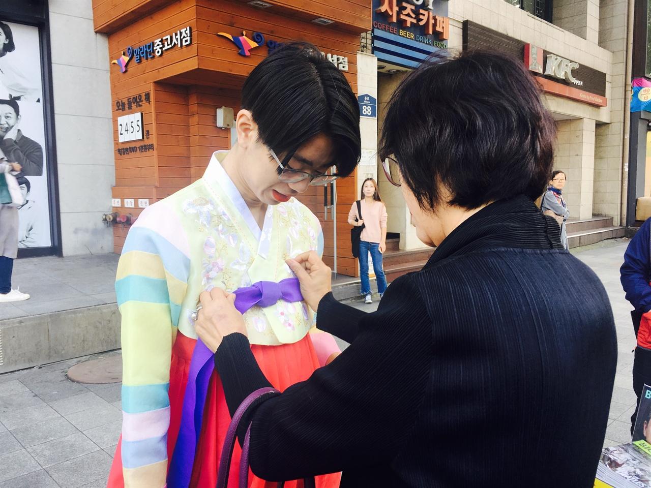 지나가던 시민이 참가자의 옷고름을 고쳐매주고 있다