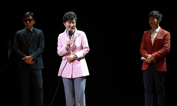 박근혜 대통령이 '문화가 있는 날' 행사의 일환으로 2014년 8월 27일 오후 서울 종로구 상명대학교 상명아트센터에서 열린 융복합 공연 '하루(One Day)'를 관람하기에 앞서 무대에 올라 인사말을 하고 있다. 왼쪽은 차은택 공연 총연출자, 오른쪽은 사회자 허경환. 이 공연은 견우와 직녀의 만남을 주제로 한 것이다.