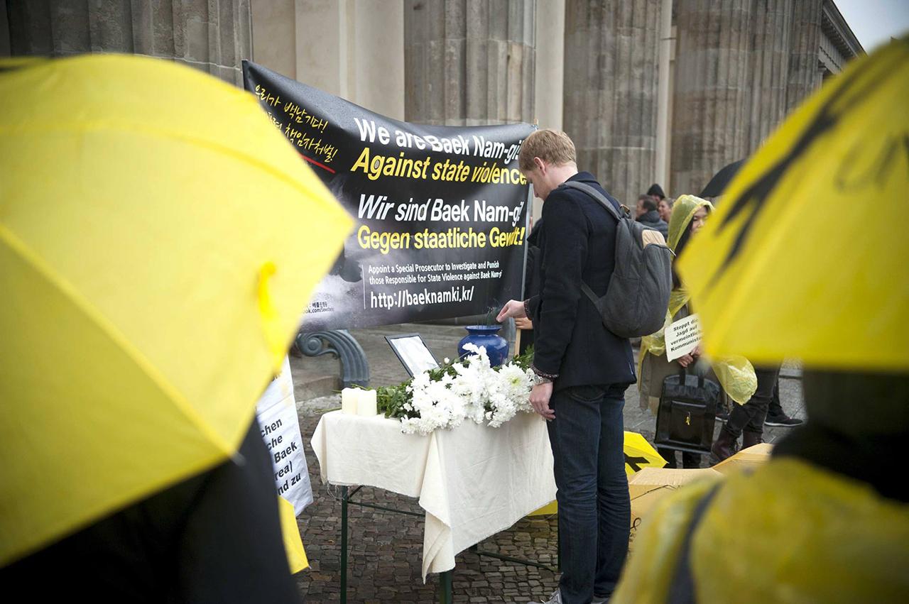 베를린의 백남기 분향소  독일인이 베를린에 설치된 백남기 분향소 앞에서 추모하고 있다.