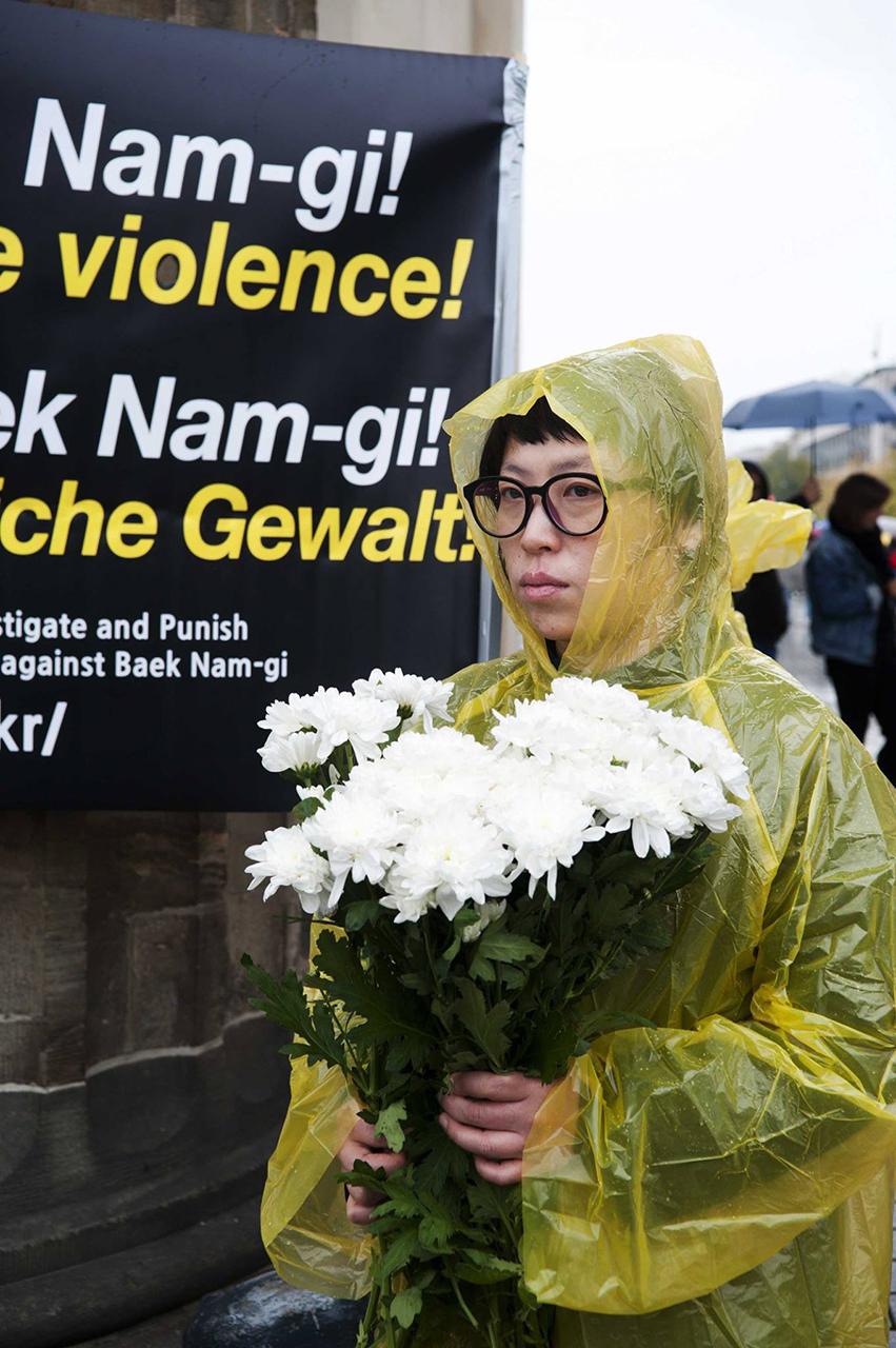 베를린 백남기 분향소 백남기 농민을 추모하기 위한 국화꽃을 들고 있는 모습