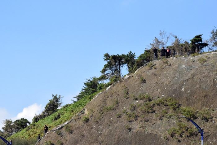 고공농성자들이 절벽 위로 진입을 시도하는 경찰과 대치하고 있다.