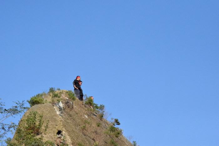 좁고 가파른 절벽 위에 선 화물 노동자들