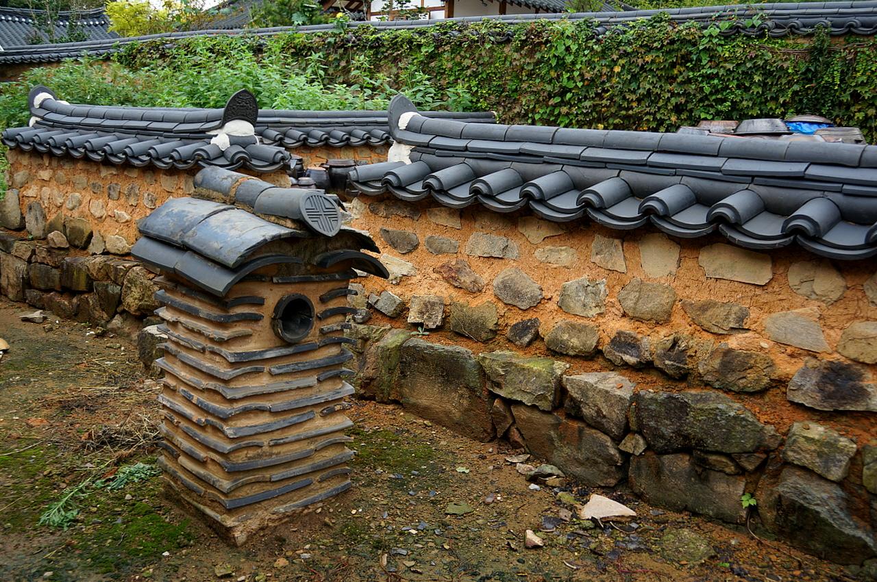 홍기응 가옥 안채 뒤 낮은 굴뚝  굴뚝 벽면에 연기구멍을 만들고 암키와로 굴뚝 몸에 줄무늬를 내고 연가를 장식하였다.