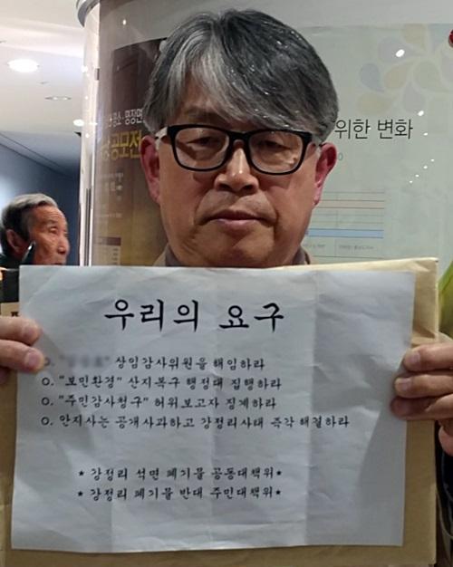 이상선 강정리 석면 폐기물 공동대책위원회 공동대표가 주민들의 요구사항을 들어 보이고 있다.